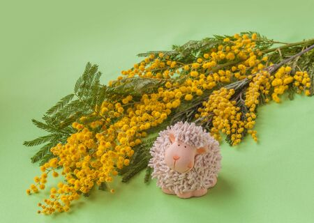 easter background: Easter background with mimosa and lamb figurine (mass produced)