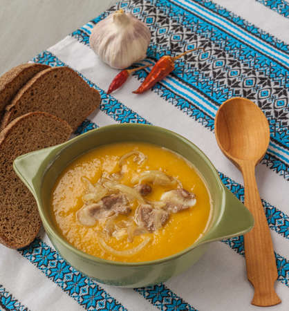 Plate with pumpkin soup with fried onions and meat  and pieces of rye bread