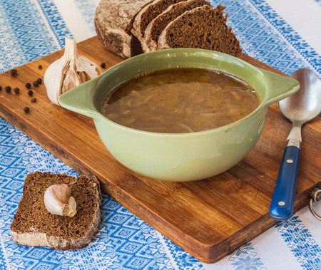 Plate with pumpkin soup with fried onions and meat close to the pot and pieces of rye bread photo