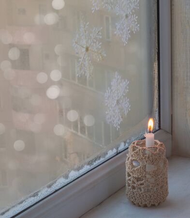 burning time: Burning candle a winter window, Christmas time. The eve of the first Advent