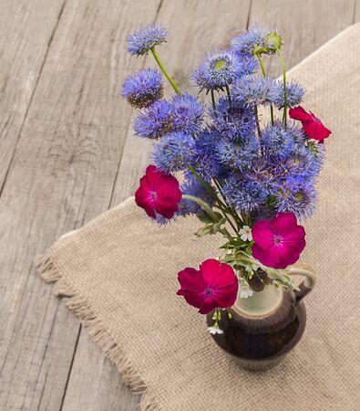 globular: Bouquet of blue Globular (Globularia) flowers on old wooden table Stock Photo