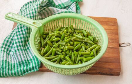 leguminous: Colander with leguminous of green raw beans on the cutting board on the kitchen table