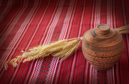 sheaf: Clay pot covered with a lid and wheat sheaf on the background fabric pattern Ukrainian