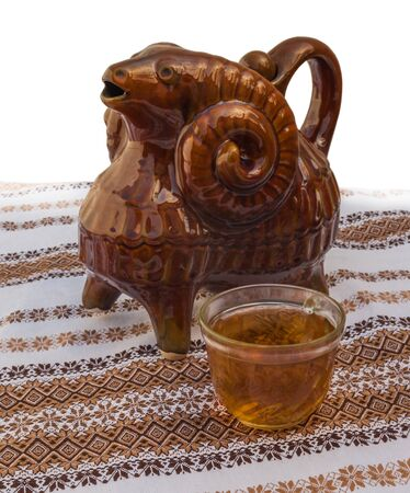 wine trade: Traditional folk Ukrainian vessel for wine or water of kumanez on embroidered on the tablecloth next to the cup. production in mass production in the the national traditions Stock Photo