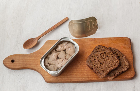 omega: Open cans of canned liver cod and slices of rye bread on a cutting board