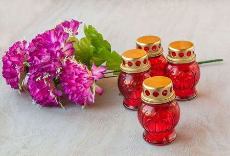 gravestones: Four gravestones red glass candlestick and branch of artificial flowers on a gray wooden background