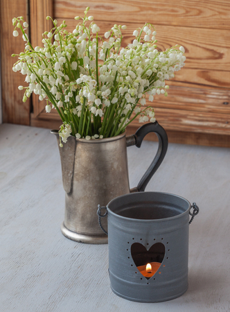 majalis: Lilies of the valley (Convallaria majalis) next to candlestick with burning candles on o the window
