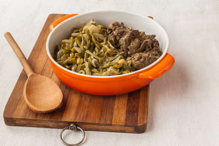 higado de pollo: Fried chicken liver and garnish green green beans with onion in a pan on the kitchen table