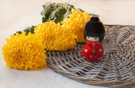 lunar month: The concept of a Japanese holiday chrysanthemums ninth of the ninth lunar month of the traditional Japanese doll Kokeshi (mass production) Stock Photo