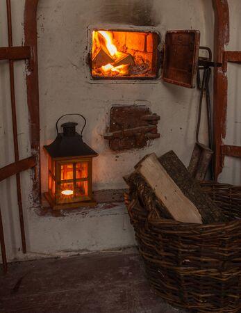 log basket: Lantern near an open fireplace and a basket of firewood Stock Photo