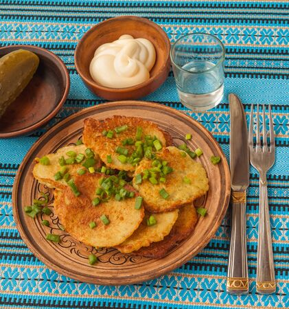 epicure: Traditional Ukrainian homemade potato pancakes, green spring onions with sour cream and glass of vodka