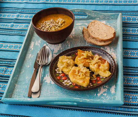 polish lithuanian: Dish Lithuanian, Polish, Belarusian cuisine rhombuses potato with fried onions  and pumpkin soup on the tray Stock Photo