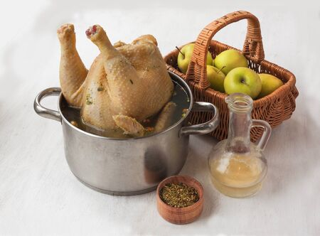 carcass meat: Marinating goose in vinegar in a pan next to a basket of apples Stock Photo