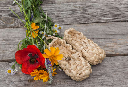 bast: The concept of summer with a bouquet of summer flowers and bast shoes with a snail on a wooden background