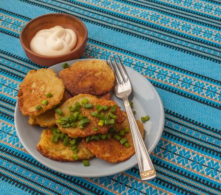 green onions: Traditional Ukrainian homemade potato pancakes potato and green onions with sour cream Stock Photo