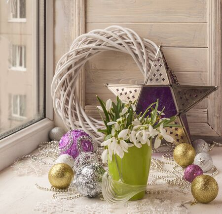 winter flower: Bouquet of snowdrops and tree toy (product of mass production) in the window