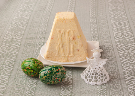 the feast of the passover: Traditional curd Easter cake with the letters XB Christ has risen on embroidered tablecloth next to the angel and Easter eggs painted in traditional folk style. (Production of mass production)