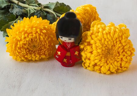ninth: The concept of a Japanese holiday chrysanthemums ninth of the ninth lunar month of the traditional Japanese doll Kokeshi (mass production) Stock Photo