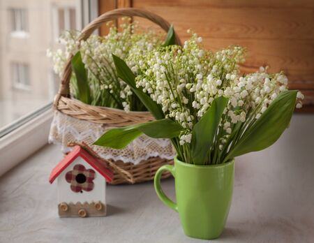 majalis: Cup and basket with lilies of the valley (Convallaria majalis) next to decorative birdhouse on o the window Stock Photo