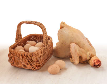 carcass: Ruwe kip karkas huis op de achtergrond mand met eieren op de keukentafel