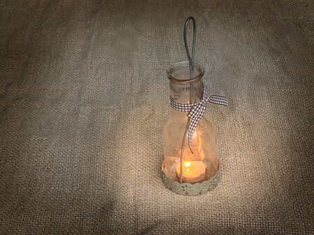 outmoded: Vintage glass lamp with a burning candle on a canvas background