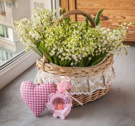 majalis: Basket with lilies of the valley (Convallaria majalis) next to heart and doll in the stroller (out production of mass production) on o the window