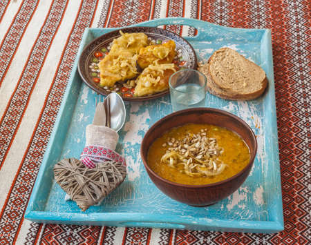 polish lithuanian: Dish Lithuanian, Polish, Belarusian cuisine rhombuses potato with fried onions, glass of vodka  and pumpkin soup on the tray