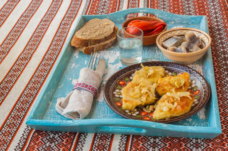 polish lithuanian: Dish Lithuanian, Polish, Belarusian cuisine rhombuses potato with fried onions, a glass of vodka and herring on the tray