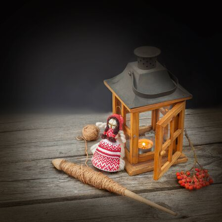 metier: Spindle  and old wooden lantern on a wooden background. The concept of ancient seasonal customs Stock Photo