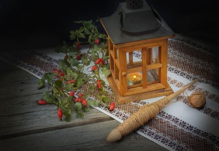 metier: Spindle, a branch of wild rose and old wooden lantern on a wooden background. The concept slavs from the late autumn started large seasonal winter work: spinning, weaving, sewing, embroidery.