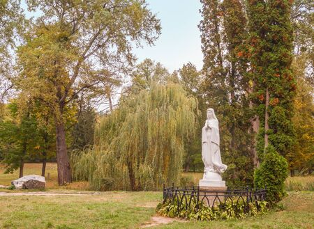 UKRAINE, BELAYA TSERKOV - October 4, 2016: The sculpture of the Virgin Mary on the island of Roses on the background of the old trees in autumn day in the Park of Alexandria in Belaya Tserkov, Ukraine