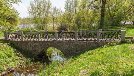 The old stone bridge in the arboretum Alexandria against the backdrop of the river Ros spring Editorial