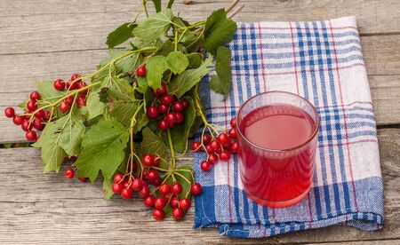 guelder rose berry: Glass of drink and a bunch of viburnum berries on the wooden background