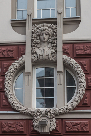 facilitate: Decoration of the Art Nouveau house in Kiev, Ukraine, a womans face with a lush hairstyle and ornaments. Stock Photo