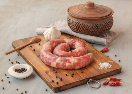 Ring of raw pork sausage on a cutting board with pepper, and garlic. Ukrainian folk cuisine