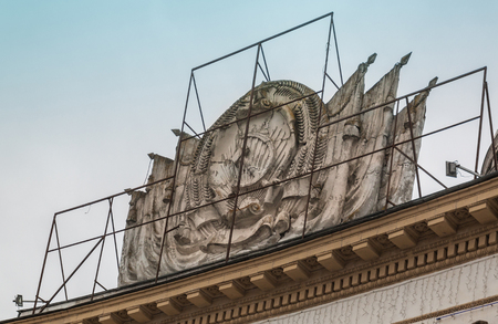KIEV, UKRAINE-26 FEBRUARY 2017: Collapsing coat of arms of the USSR, which consisted of Ukraine, on the facade of a house in Kiev
