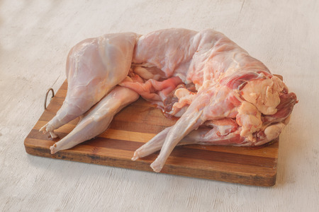 Carcass of raw uncooked rabbit on a cutting board