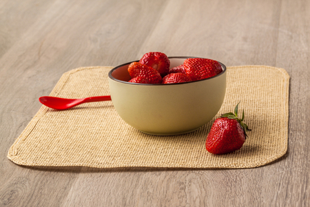Berry strawberries in a ceramic bowl on a wooden table