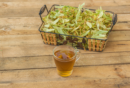 Flowers of a linden and transparent mug of lime tea on a wooden table Foto de archivo - 104455556