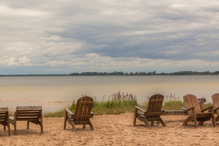 Old wooden sunbeds under a cloudy sky on the beach at Lake Svitiaz