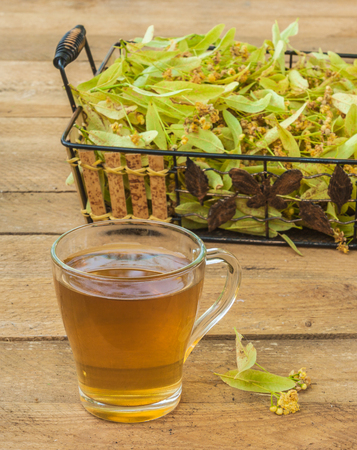 Flowers of a linden and transparent mug of lime tea on a wooden table Foto de archivo - 108732133