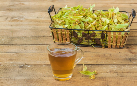 Flowers of a linden and transparent mug of lime tea on a wooden table Foto de archivo - 108732134