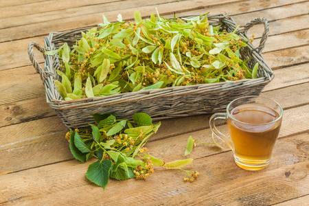 Flowers of a linden and transparent mug of lime tea on a wooden table Foto de archivo - 108732135