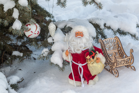 Toy Father Frost under the snow-covered tree (mass produced products) Stock Photo