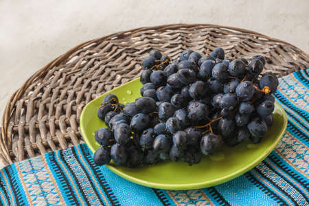 Bunches blue table grapes on a plate.