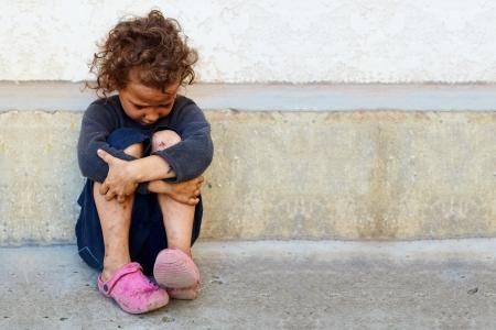 貧しい人々、悲しい子少女コンクリート壁に座っています。