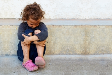 indigence: poor, sad little child girl sitting against the concrete wall