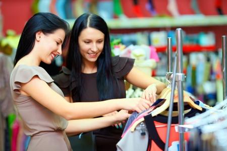 chicas comprando: dos sonriente a mujer de compras en tienda al por menor