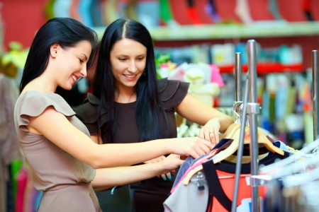 clothing store: two smiling woman shopping in retail store Stock Photo