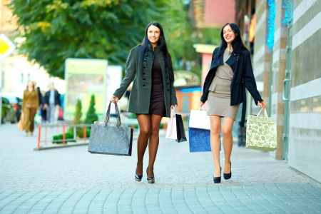 happy women walking the city street with shopping bags photo